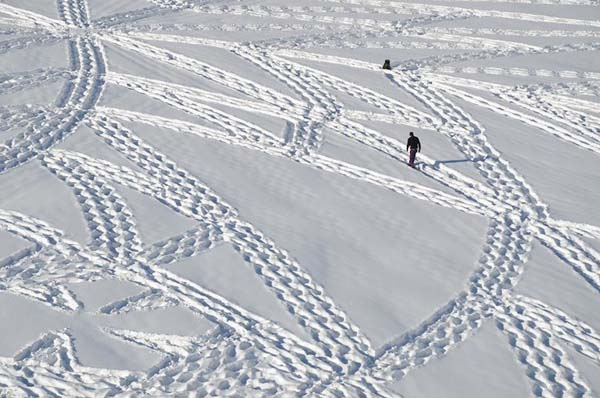 Simon walks over layers of fresh snow in special shoes to create his mind-boggling art.